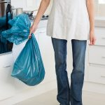 Low section of a young woman carrying garbage bag in the kitchen