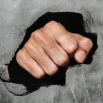Fist breaking old concrete wall, focus on fist