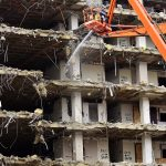 Building collapsing or being demolished with debris falling down